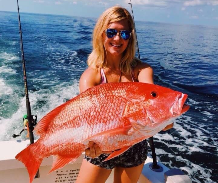 A young lady showing a beautiful red snapper